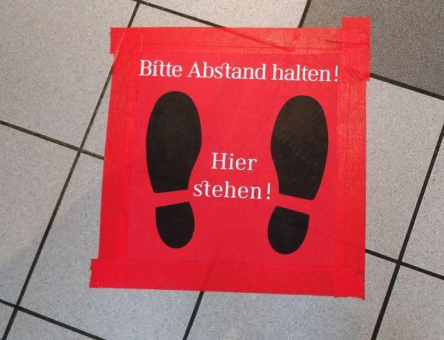 """Fußboden aus hellen Steinplaten. Darauf ein großer roter Aufkleber mit dem Text """"Bitte Abstand halten - Hier stehen"""" mit zwei schwarzen Fußabdrücken."""