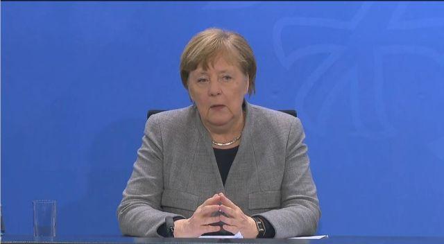 Angela Merkel sitzend, Hände zur Raute geformt, im grauen Oberteil vor blauem Hintergrund.