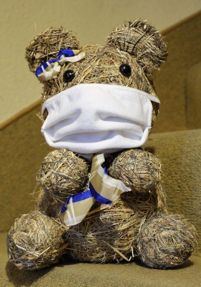 Ein Bär aus Heu mit einer weißen Schutzmaske über Mund und Nase.