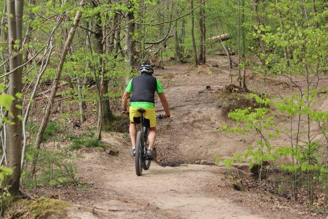 Person fährt mit dem Mountainbike auf einer braunen festen Fläche: früher ein Trampelpfad, heute eine breite Piste.