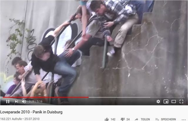 Menschen versuchen sich an Metallteilen hochzuziehen, um dem tödlichen Gedränge zu entgehen.
