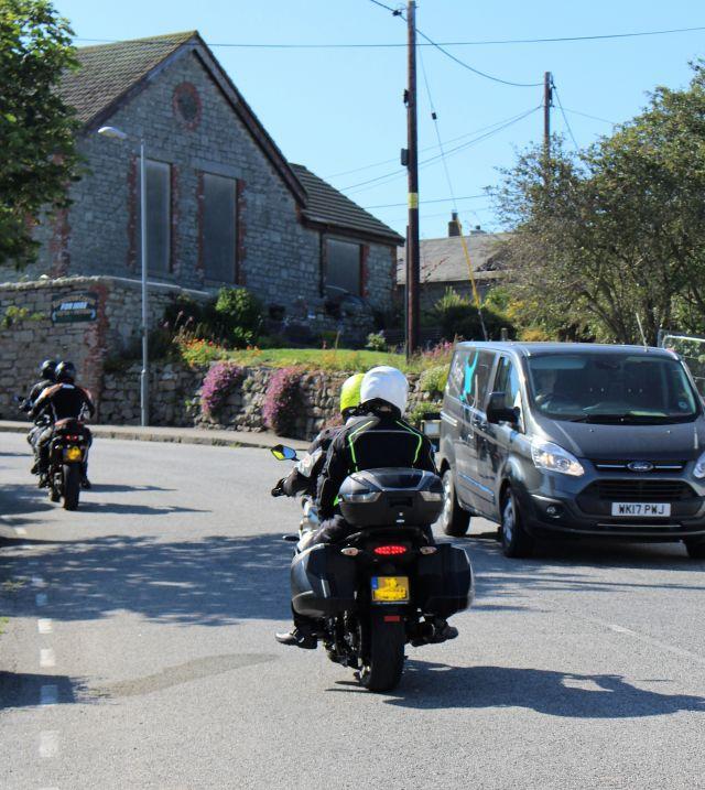 Zwei Motorräder fahren durch eine enge Straße in St. Just.