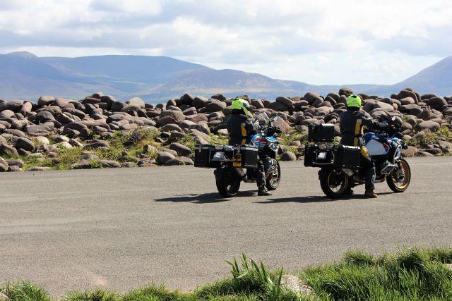 Zwei Motorradfahrer vor vom Meer aufgetürmten abgerundeten Felsbrocken.