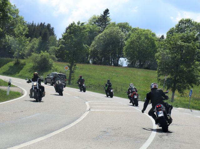 In einer leichten Kurve fahren vier Motorradfahrer hinter einem Auto her, zwei Motorradfahrer komen entgegen.