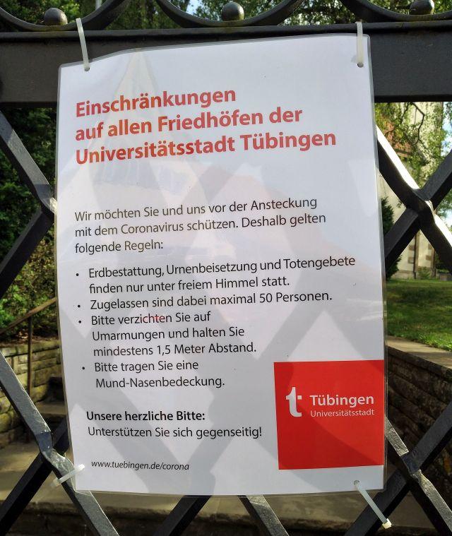 """Hinweisschild am Friedhofstor: """"Bitte verzichten Sie auf Umarmungen und halten Sie mindestens 1,5 Meter Abstand."""""""