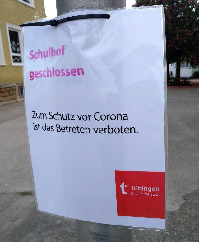 """Kleinplakat mit dem Text """"Schulhof geschlossen"""" in roter Farbe und """"Zum Schutz vor Corona ist das Betreten verboten"""" in schwarzer Farbe. Hinweis der Stadtverwaltung Tübingen."""