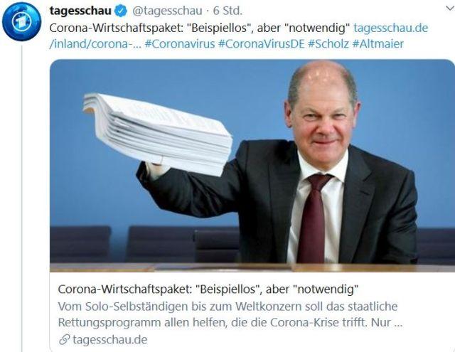 Olaf Scholz grinst ud hält ein dickes Papierbündel hoch.