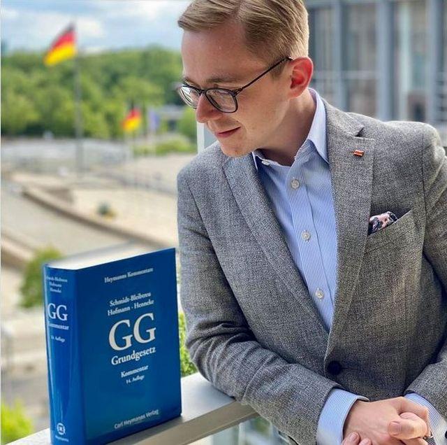 Philipp Amthor im grauen Anzug mit offenem blauen Hemd. Leicht verzückt betrachtet er eine blau eingebundene Ausgabe des Grundgesetzes.
