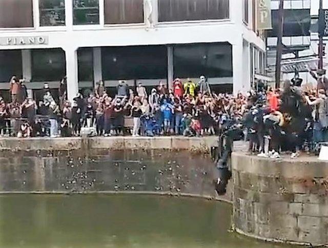 Eine Statue wird von vielen Personengemeinsam in Bristol ins Hafenbecken gestürzt.