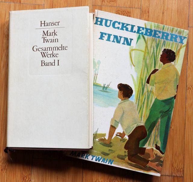 Zwei Buchcover: Eine ca. 60 Jahre alte Jugendausgabe von Huckelberry Finn mit zwei Personen auf dem Titel. Die zweite Ausgabe ist ein Band aus einer Gesamtausgabe von Mark Twain..