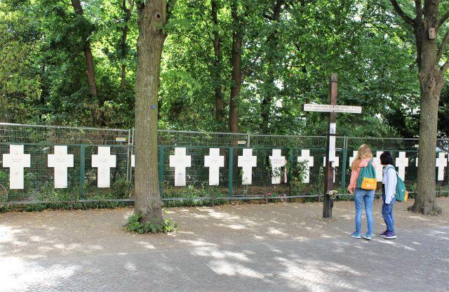 Weiße Kreute in der Nähe des Brandenburger Tors erinnern an die an der Mauer getöteten Flüchtlinge. Zwei junge Frauen informieren sich gerade.