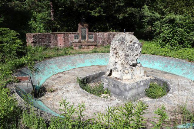 Denkmal für Michael Knoll. Im blau bemalten Brunnen ohne Wasser steht ein großer Tuffstein. Der Brunnen wächst zu, einzelne Teile sind zerbrochen.