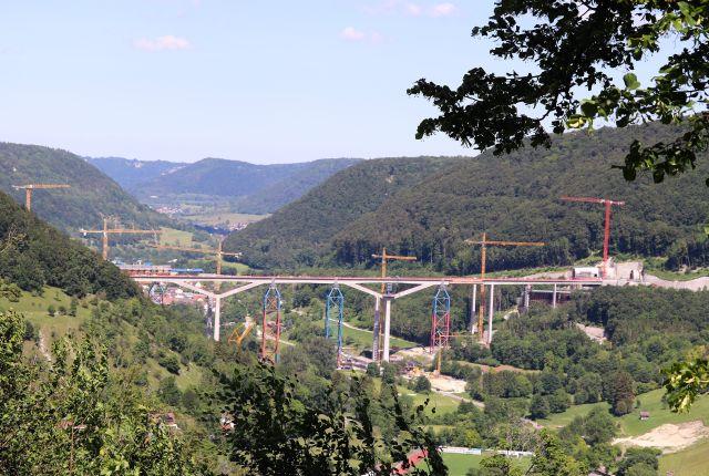 Eine Brücke für die Schnellbahntrasse ist bereits über dem Filstal errichtet worden. Die zweite ist im Bau. Zahlreiche bunte Kranen.
