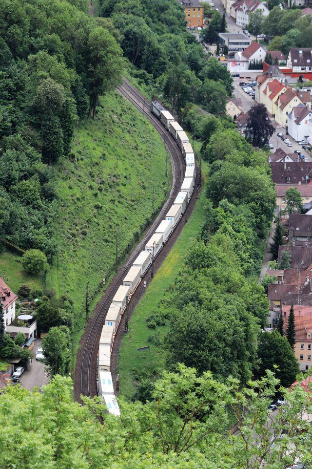 Ein langer Güterzug mit hellen Waggons fährt die Geislinger Steige hoch.