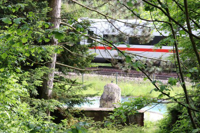 Silberner ICE mit rotem Längsbalken fährt am Knoll-Denkmal vorbei.