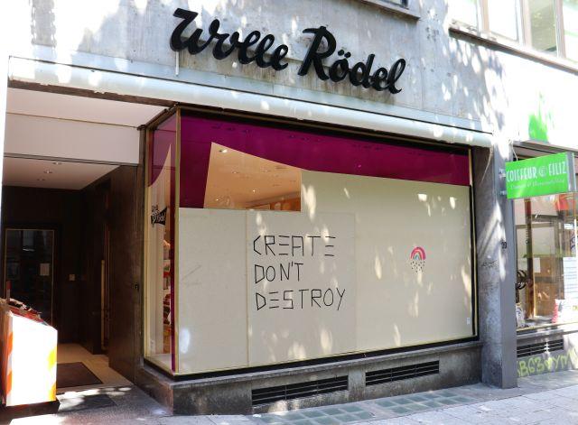 Laden mit Aufschrift 'Wolle Rödel'. Die eingeschlagene Schaufensterscheibe ist durch Holzplatten ersetzt. Darauf steht als Graffiti 'Create Don't destroy'.