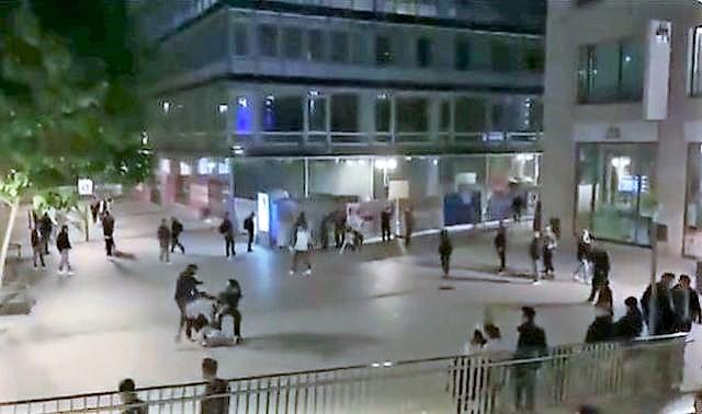 Eine Person greift einen Polizisten an. Er springt ihm mit gestrecktem Bein gegen den Oberkörper.