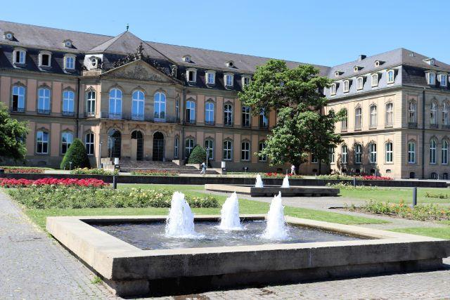 Quadratische Wasserspiele mit drei kleinen Fontänen. Die Steinumrandung lässt keinen Zugang für Insekten, Eichhörnchen oder Igel zu. Im Hintergrund das Neue Schloss in Stuttgart.