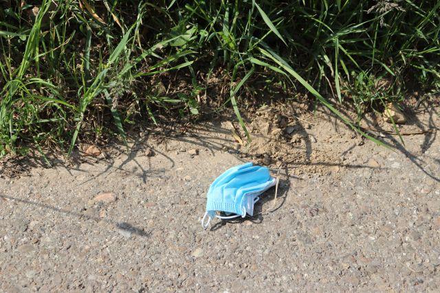 Blaue Mund-Nasen-Maske gegen Coronaviren auf einem Feldweg.