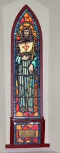 Buntes Glaskichenfenster mit einer Darstellung des Heiligen Brendan, der ein Segelboot im Arm hält.