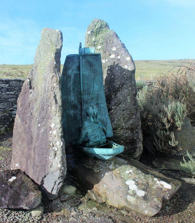 Grünlich schimmernde Metallskulptur: Person sitzt in einem Segelboot. Links und rechts ein Felsbrocken.