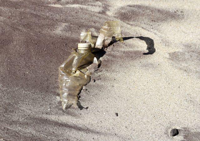 Eine zerfallende Kunststoffflasche mit weißem Drehverschluss mit Seetang auf Sandstrand.