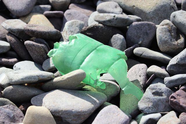 Rest einer grünen Kunststoffflasche auf großen vom Meer abgerundeten grauen Steinen.