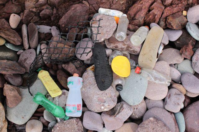 Durchsichtige, gelbliche und grüne Plastikflaschen und andere Kunststoffteile an einem steinigen Strand.