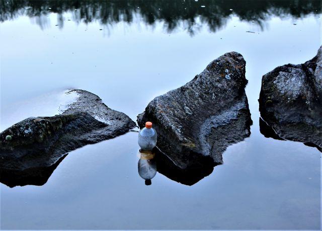 Eine helle Pet-Flasche mit rotem Drehverschluss treibt senkrecht im Neckar zwischen großen Felsbrocken.