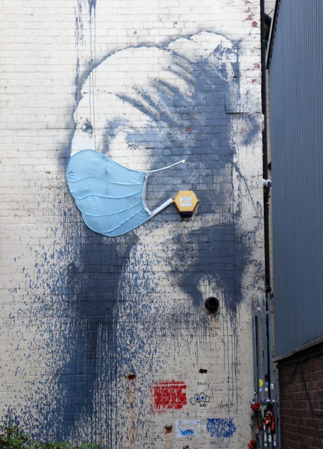 Ein Frauengesicht - jetzt mit Maske. Ursprünglich stand der Signalgeber einer Alarmanlage im Vordergrund, den Banksy als Ohrring in das Bild integrierte.