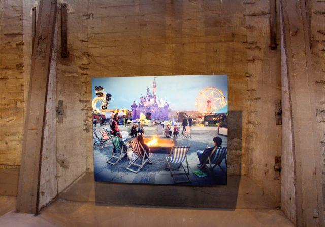 Vor einer bräunlichen strukturierten Wand hängt ein buntes Foto mit Menschen in Liegestühlen und dahinter einem vermeintlichen Freizeitpark.