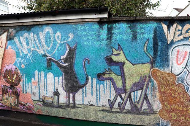 Zwei Hunde auf vier Pfoten, ein dritter auf den Hinterbeinen mit einer Spraydose.