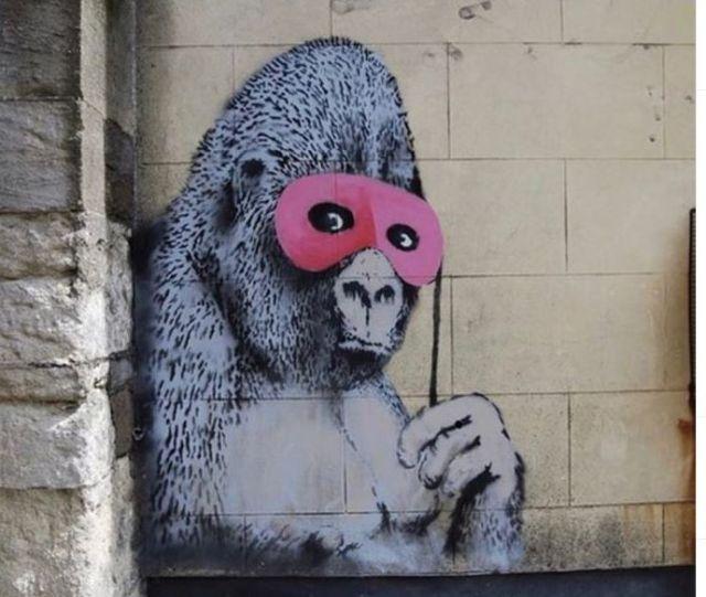 Gemaltes Bild eines Gorillas mit einer pinkfarbenen Brille an einer Hauswand.