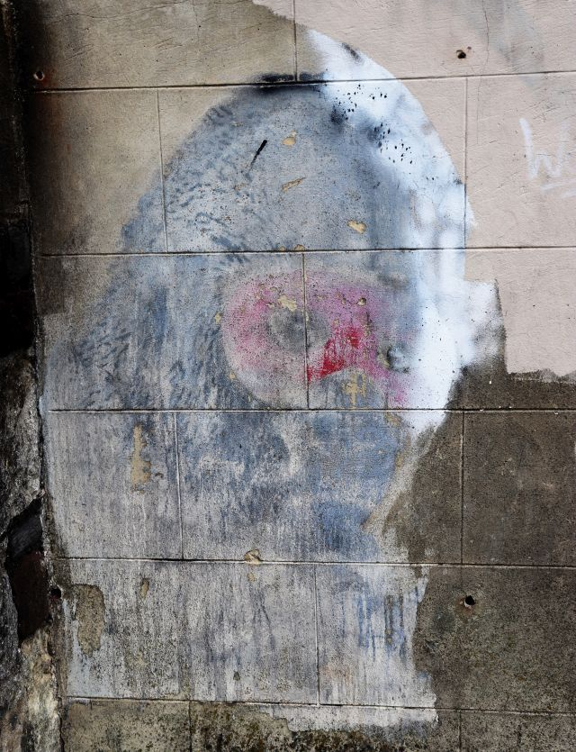 Das Gemälde eines Gorillas an einer Hauswand. Es wirkt wie verblichen. Es wurde übertüncht und wieder freigelegt.