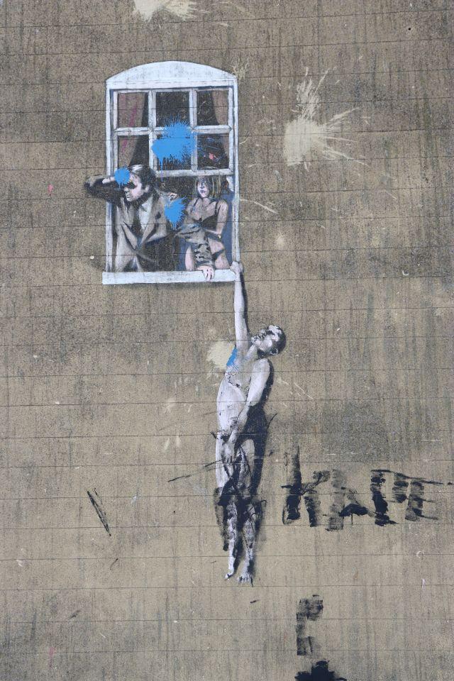 Ein Mann schaut aus einem Fenster, die Frau in Unterwäsche, am Fenstersims hängt mit einer Hand eine Männergestalt. Mit der linken Hand bedeckt er sein Geschlechtsteil. Blaue Flecken an der Fassade gehen auf Würfe von Farbbeuteln zurück.