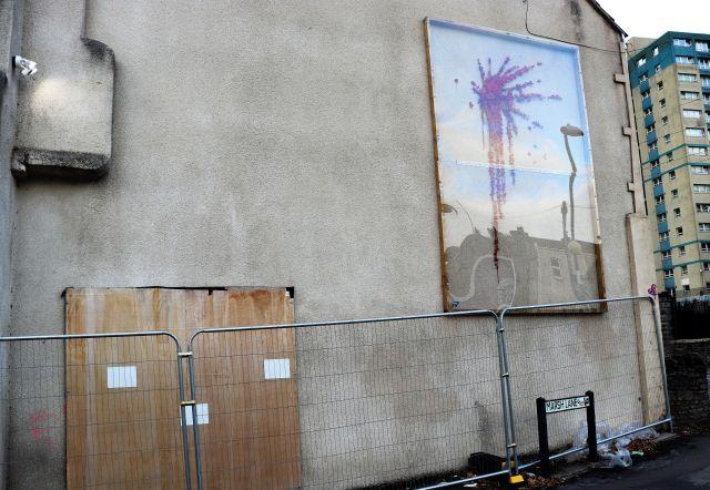 Graue Hausfassade. Im unteren Bereich verdecken Holzplatten einen Teil des Banksy-Werks (Mädchen mit Schleuder), im oberen Bereich hinter einer Plastikfolie:rote Blumen, die sich aus dem hochgeschleuderten Objekt ergießen.