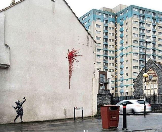 Ein Mädchen schießt mit einer Schleuder ein Objekt an die Fassade, und daraus ergießen sich rote Blumen. Links im Hintergrund ein Hochhaus.