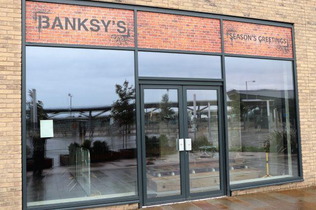 Über einem Ladenfenster steht 'Banksy's Season's Greetings', doch die Türen sind zu, die Fesnter spiegel und sind schmutzig.