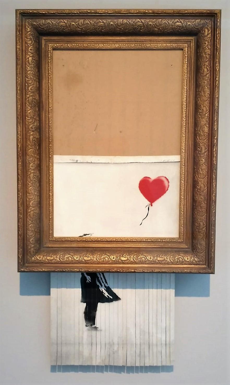 Aus einem goldfarbenen dicken Bilderrahmen ragt ein zeilweise geschreddertes Bild heraus. Im oberen Teil der rote Ballon, unten der Teil einer Mädchengestalt.