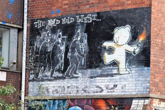 Ein heller Teddybär wirft einen Molotowcocktail auf Polizisten, die mit Schutzschildern vorrücken, aber auf dem Kopf haben sie den üblich Bobby-Helm.