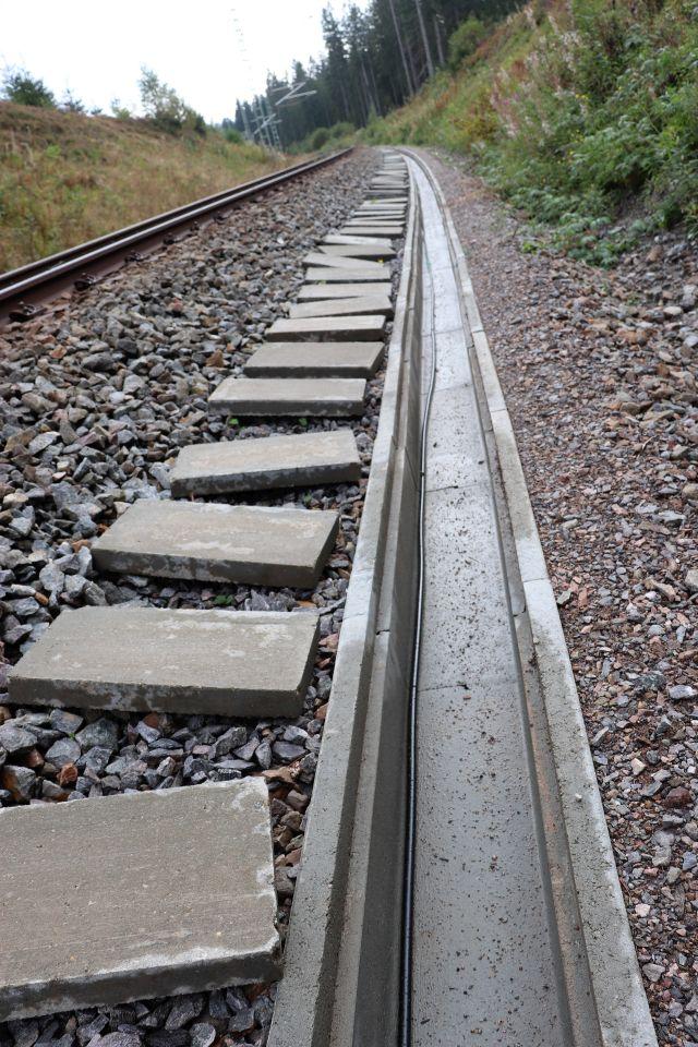 Grauer Betonkanal, daneben auf dem Schotterbett die Platten, die ihn ansonsten verschließen. Links Schienen.