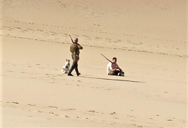 Zwei Männer mit Gewehren und einem Hund auf einer Sandfläche.