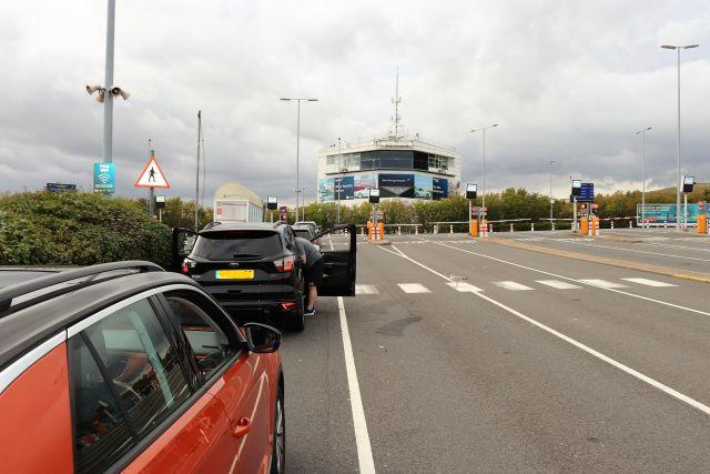 Vier Fahrzeuge warten auf dem Parkplatz des Eurotunnels auf den nächsten Zug. Der restliche Parkplatz ist leer.