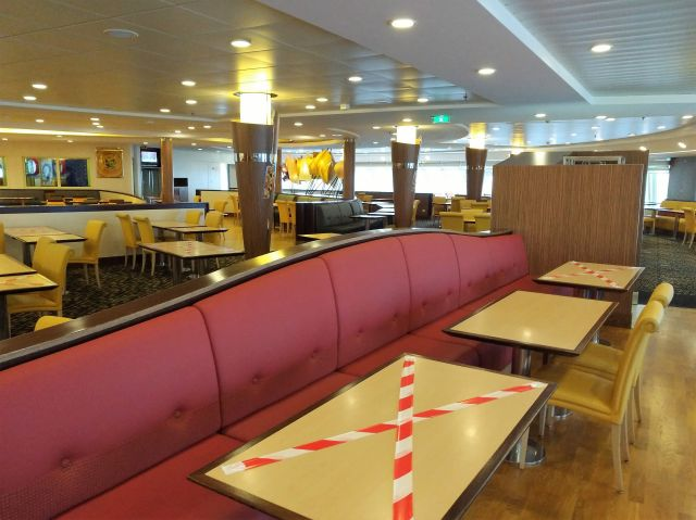 Einige Tische in einem Restaurant auf einer Fähre mit weiß-roten Warnbändern gesperrt. Aber der ganze Raum ist ohne jeden Gast.