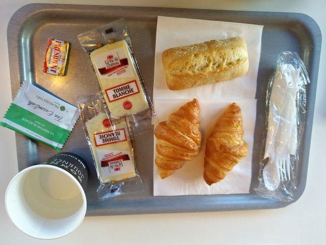 Graues Tablett mit eingepacktem Käse und Einmalbesteck in Plastikhülle.