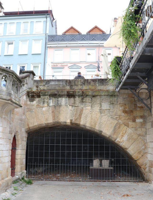 Dunkler Raum unter einem Torbogen mit zwei erkennbaren Teilen des früheren Klosters.