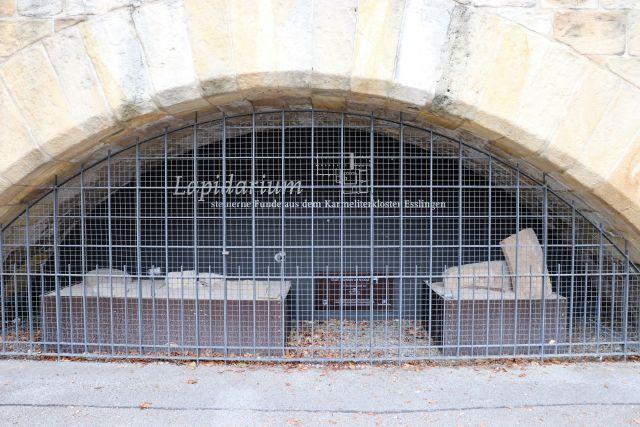 Unter einem Torbogen aus beschlagenen Steinquadaern zwei Ausstellungsstücke des Esslinger Lapidariums hinter einem engmaschigen Gitter.