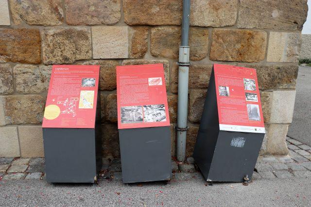 Drei rot-graue Infosäulen mit Fotos und Texten.