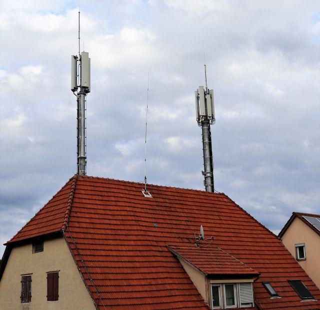 Zwei große helle Antennensysteme auf einem roten Ziegeldach.