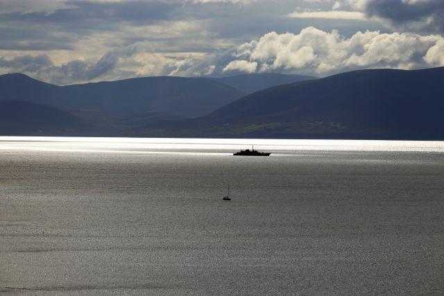 Ein Marineschiff auf spiegelglattem Meer. Im Hintergrund dunkle Berge und weiße Wolken.